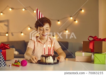 Happy smiling boy in festive cap sitting and looking at birthday holiday cake with candles 70863235