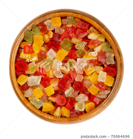 Diced candied fruits in a wooden bowl. Peel of oranges, papayas and succade, preserved and sweetened in sugar syrup, used as a filling or as a garnish. Close-up from above, isolated, macro food photo. 70864696