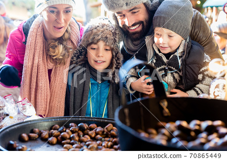 Family on Christmas market eating sweet roasted chestnuts 70865449