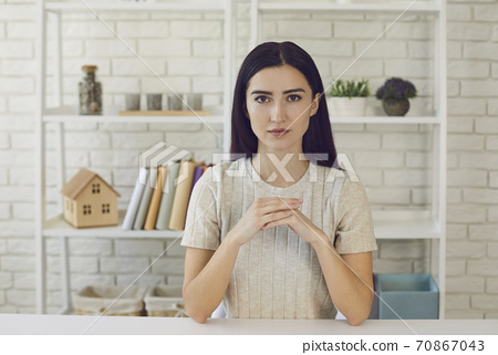 Portrait of young serious brunette patiently looking in camera. Home interior in blurred background. 70867043