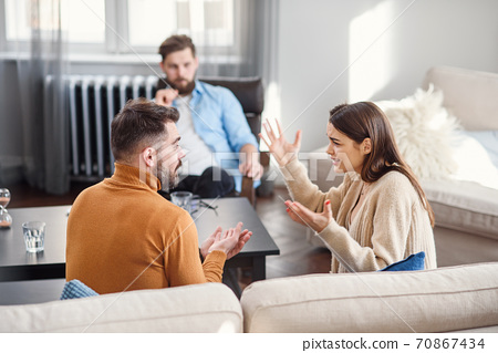 Young fighting angry couple blaming each other for problems, telling its your fault, discussing with psychologist who is right and wrong, misunderstanding and selfishness in marriage. 70867434
