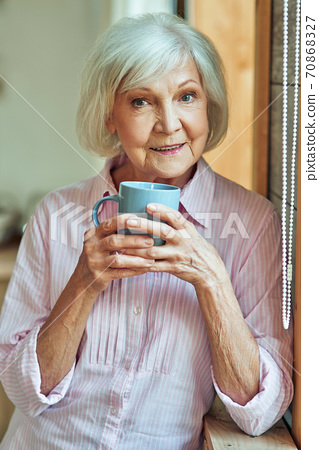 Happy stylish gray haired lady standing near window with cup 70868327