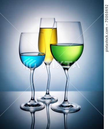Wine glasses with colored liquid with reflection on a colored background. 70868692