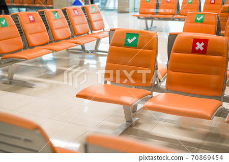 Row of empty bench chair seats in public transportation terminal with social distancing guidance during Coronavirus pandemic. Covid-19 safety advice to prevent virus spread concept 70869454