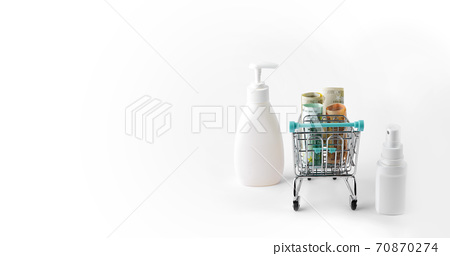 a small shopping cart filled with banknotes, with bottles of disinfectant nearby 70870274