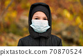 Boy in medical mask on the street 70870524