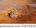 Muddy ground with spring water, with stacks of stones on one side. 70870848