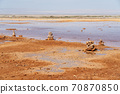 Muddy ground with spring water, with stacks of stones on one side. 70870850