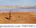 Muddy ground with spring water, with stacks of stones on one side. 70870851