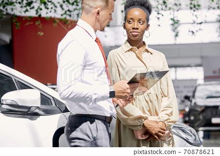 confident caucasian salesperson selling cars at car dealership 70878621