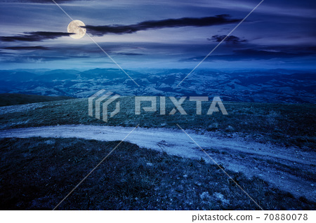 mountain road through grassy meadow at night. wonderful summer adventure in full moon light. clouds on the blue sky 70880078