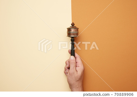 copper prayer drum on a stick in a male hand on a brown background 70889906