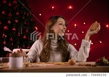 Pretty smiling brunette girl making christmas gingerbread alone, new normality 70890250