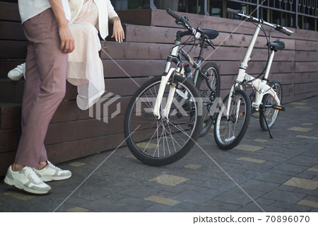 View on man legs standing beside two bicycles on a sidewalk 70896070