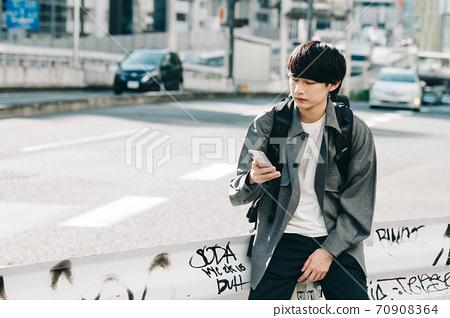 一個二十多歲的男人看著智能手機 70908364