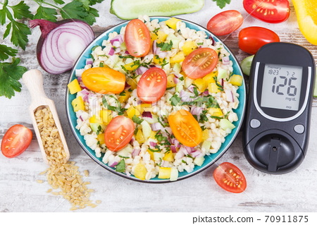 Glucose meter with sugar level, salad with vegetables and bulgur groats, tape measure 70911875