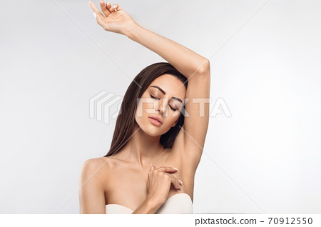 Armpit epilation, lacer hair removal. Young woman holding her arms up and showing clean underarms, depilation  smooth clear skin .Beauty portrait. 70912550