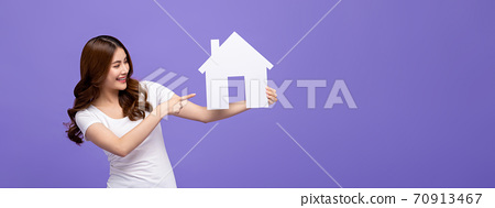 Happy beautiful Asian woman smiling and pointing to house cutout model 70913467
