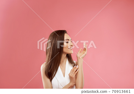 Beautiful model girl with a beige French manicure nail . Fashion makeup and care for hands and nails and cosmetics. Beauty Young Woman with Clean Fresh Skin close up . Skin care face . 70913661