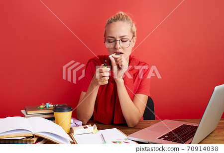 young caucasian blonde female smoke cigarette at work place 70914038