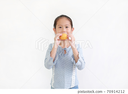 little asian child girl hold and eating Custard Cake isolated on white background. 70914212