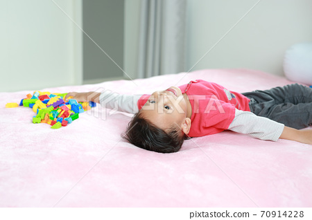 Adorable asian little baby boy playing colorful plastic blocks and lying on bed. 70914228
