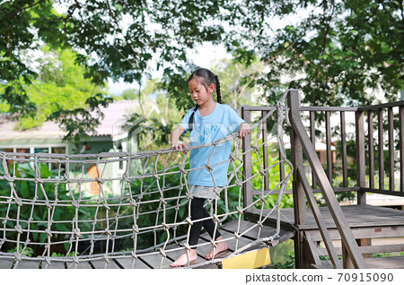 Asian little girl playing on suspension wooden bridge. Kid walking on rope bridge 70915090