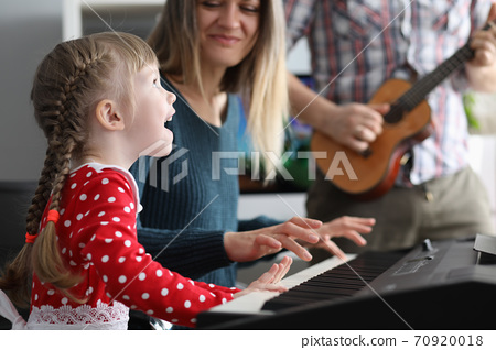 Little beautiful girl sings song is played on piano together with her parents portrait 70920018
