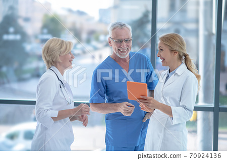Smiling doctors studying something on tablet, having friendly conversation 70924136