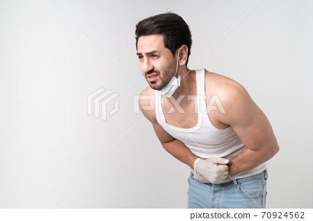Coronavirus panic sick man wearing mask holding his stomach feeling pain stress and worry with copy space, COVID-19 pandemic, self-protected, panic and stress, self-quarantine, scare and worry. 70924562