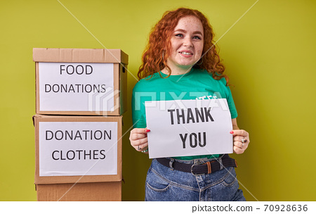 beautiful redhead volunteer woman collecting donation for poor 70928636