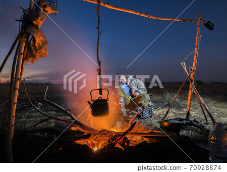 A man dozing off after a hunt near a fire with a kettle 70928874