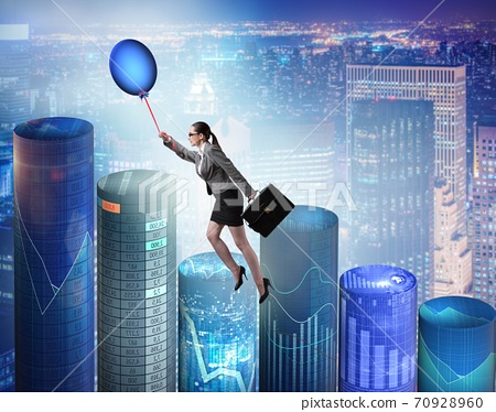 Businesswoman flying on hot balloon over graph 70928960