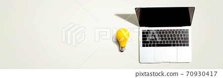 Laptop computer with a yellow light bulb 70930417
