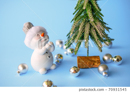 Snowman on a blue background and on the background of a Christmas tree. Toy snowman dreams, makes a wish on new year's eve. snowman decorates Christmas tree with Christmas toys 70931545