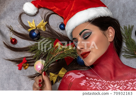 A beautiful brunette with artistic make-up and wearing a Santa Claus hat 70932163
