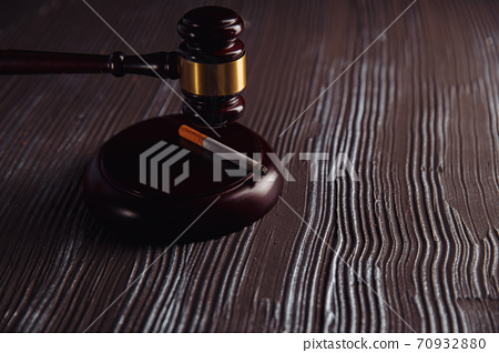 Judge gavel and smoking cigarette in a dark room. Tobacco law 70932880