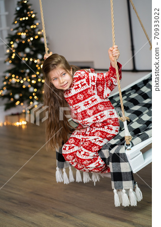 A little girl in pajamas can't sleep on a festive night. Christmas magic fairy tale. Happy childhood 70933022