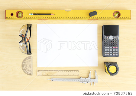 Top view engineer desk light brown wood texture have roll home plan and tools, measuring tape , calculator, vernier caliper copy space.House plan on wood table architect have safety glasses and workpl 70937565
