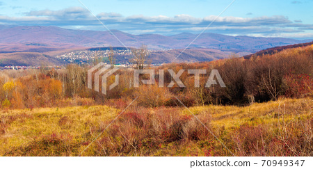 rural valley in the morning. beautiful autumn scenery in mountains. town in the distant valley. clouds on the blue forenoon sky 70949347