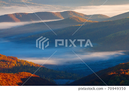 rising clouds in mountainous countryside at sunrise. gorgeous view of autumn fog in valley 70949350