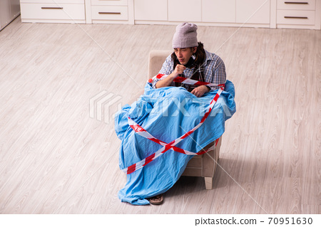 Young sick man suffering at home in pandemic concept 70951630