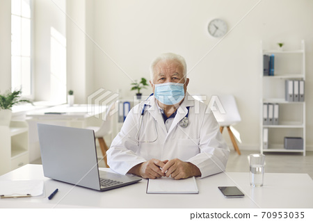 Senior experienced doctor in uniform sitting near laptop during videocall and online meeting 70953035