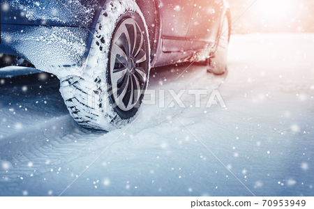 Car tires on winter road covered with snow 70953949
