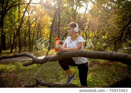 Disabled woman walking down and training outdoors in forest 70953963
