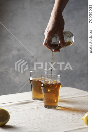 Woman pouring black hot tea 70959033