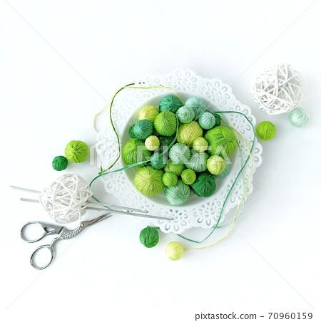 White basket with green knitting yarn. 70960159
