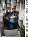 Thoughtful mature businessman in eyeglasses drinking coffee 70960200