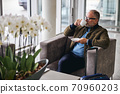 Mature tourist drinking coffee in the waiting area 70960203
