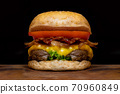 Close up fresh tasty the hamburger with cheese, tomato, beef, bacon and green salad vegetable, selective focusing technical, wooden table and darkness background. 70960849